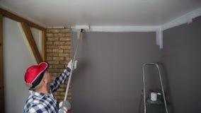 Lack-Rolle mit Lackproben Ein Mann in einem roten Hut, der einen Raum mit einer Farbenrolle und -Pinsel färbt stock footage