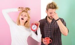 Lack of sleep. Couple sleep not enough time. Family drink morning coffee yawning faces. Couple oversleep awakening hold. Alarm clock. Hate morning awakening stock photo