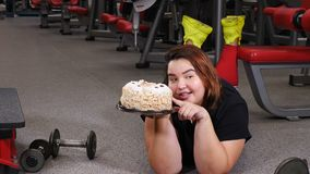 Lack of willpower. diet, fitness, healthcare. Portrait of obese young woman struggling with cake desire in gym. Sport. With unhealthy food. active life with stock footage