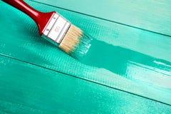 Lacka en trähylla genom att använda målarpenseln royaltyfri fotografi
