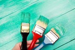 Lacka en trähylla genom att använda målarpenseln royaltyfria foton
