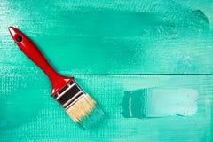 Lacka en trähylla genom att använda målarpenseln royaltyfria bilder