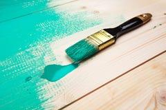 Lacka en trähylla genom att använda målarpenseln arkivfoton