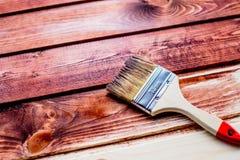 Lacka en trähylla genom att använda målarpenseln borsta och måla, befläcka, trägolvet, väggen, reparationen, återställandebegrepp royaltyfria bilder