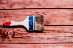 Lacka en trähylla genom att använda målarpenseln borsta och måla, befläcka, trägolvet, väggen, reparationen, återställandebegrepp fotografering för bildbyråer