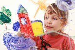 Lacke des kleinen Mädchens auf Glas, Haus, Baum Lizenzfreies Stockfoto