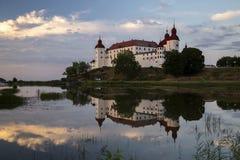 Lacko slott med reflexion i lugna vatten arkivfoto