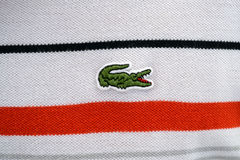Lacoste. Logo On A White Shirt With Red And Black Stripes Stock Photography