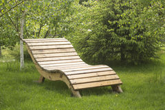 Lacquered wooden garden bench on the lawn. Lacquered wooden garden yelow bench on the lawn Stock Photo