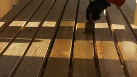 Lacquering vertical flooring boards. Impregnation and imbibition of vertically arranged wooden bars with a brush. Construction and painting works from wood stock footage
