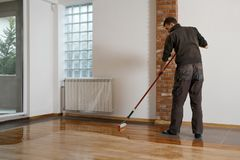 Lacquering Wood Floors. Worker Uses A Roller To Coating Floors Stock Image