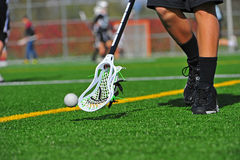 Lacrosse ball catching. Boys High School Lacrosse player catching a lacrosse ball that is close to the ground on a turf field stock photos