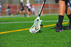 Lacrosse ball pick up. Boys High School Lacrosse player picking up a ball in a white head on a turf field royalty free stock image
