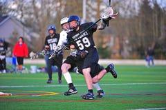 Lacrosse de los muchachos que sostiene la bola hacia fuera Fotos de archivo