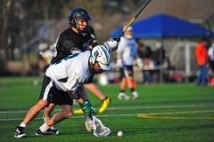 Lacrosse de los muchachos que sostiene la bola hacia fuera Fotografía de archivo