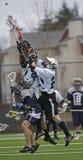 Lacrosse de los muchachos que sube para la bola Foto de archivo libre de regalías