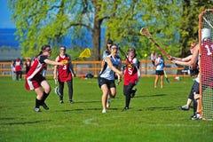 Lacrosse del equipo universitario de las muchachas tirado en meta Imagenes de archivo