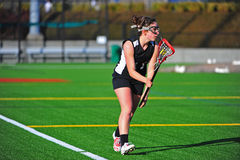 Lacrosse girl with the ball. High school Varsity girls lacrosse player cradling the ball in her stick as she looks for an open player down the field Royalty Free Stock Photography