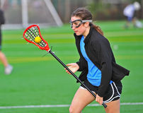 Lacrosse girl cradling the ball. High school Varsity girls lacrosse player cradling the ball in her stick Stock Photography
