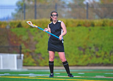Lacrosse girl cradling the ball. High school girls lacrosse player in her black uniform and socks cradling the ball Stock Photos