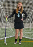 Lacrosse girl posing in front of goal Royalty Free Stock Photos