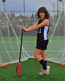 Lacrosse girl posing with her stick. High school Varsity girls lacrosse player posing in front of the goal with her stick Royalty Free Stock Images