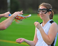 Lacrosse Girls stick check. High school girls lacrosse player holds her mouth guard and watches as the official inspects her stick before the start of the game Stock Images