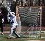Lacrosse goalie stopping the ball. A lacrosse goalie is blocking the net and stopping the ball from going into the goal during a high school lacrosse game stock photos