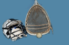Lacrosse goalie equipment. Lacrosse goalie helmet stick and ball on a blue background Stock Images