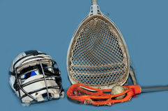 Lacrosse goalie equipment and momens stick. Lacrosse goalie helmet stick and womens stick with ball on a blue background Stock Photo
