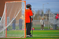 Lacrosse Goalie standing guard. Boys High School Lacrosse goalie standing guard at his post as the game continues at the other end of the field stock photos