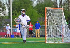 Lacrosse Goalie wiping his face. Boys High School Lacrosse goalie walking to his post by the goal royalty free stock image
