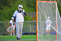 Lacrosse Goalie wiping his face. Boys High School Lacrosse goalie wipes his face after recovering from a goal royalty free stock photos