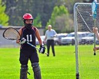 Lacrosse goalkeeper. High school girls' lacrosse goalkeeper at the goal stock photo