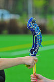 Lacrosse passing a girls stick. Game official passes a lacrosse stick back to the player after inspection before the game begins royalty free stock photo