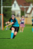 Lacrosse player after the ball. High School girls varsity lacrosse player reaching for the ball with her stick Stock Image
