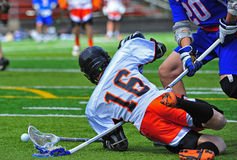 Lacrosse player down. Boys High School Lacrosse player falls down on a stick stock image