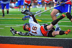 Lacrosse player falling down. The game goes on behind a Boys High School Lacrosse player who fell down after being pushed stock photos