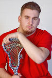 Lacrosse Player Holding onto his stick. Young man posing with his alacrosse stick wearing red shirt Stock Image