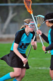 Lacrosse players. High School girls varsity lacrosse player covering team mate Stock Image
