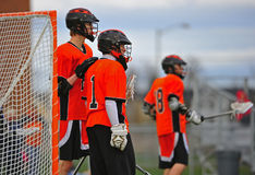 Lacrosse players support. Boys High School Lacrosse player consulting with his goalie as he rest his hand on his shoulder and they look down the field stock image