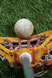 Lacrosse players view. Abstract of a players perspective with the looking down on a bright orange  girls lacrosse stick scooping up the ball on a grass field Royalty Free Stock Images