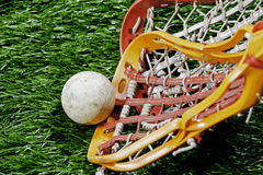 Lacrosse race for the ball. As the players race for the ball on a turf field a bright orange  girls lacrosse stick scooping up the ball on a grass field Royalty Free Stock Images