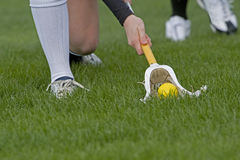 Lacrosse scooping up the ball 1. Womens Lacrosse players kneeling down to scoop up a ball durring a game on a grass field stock images