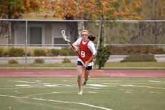 Lacrosse Sprint. A girl runs with a lacrosse stick and ball Royalty Free Stock Image