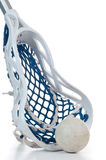 Lacrosse stick with ball. A sliver lacrosse stick with a white head and blue netting along with a gray ball Royalty Free Stock Images