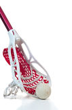 Lacrosse stick with ball. A redlacrosse stick with a white head and red netting along with a gray ball Royalty Free Stock Photography