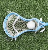 Carolina blue lacrosse stick with a ball. A lacrosse stick with a ball in it laying on the turf royalty free stock photos