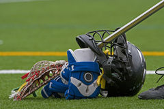 Lacrosse stick and gear. High school boys Lacrosse grear stacked on his stick durring half time Stock Image