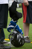 Lacrosse stick and gear. High school boys Lacrosse grear stacked on his stick durring half time Royalty Free Stock Image